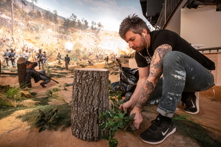 In this Friday, Feb 15, 2019 photo, a worker puts some final touches on the diorama that is part of the Atlanta Cyclorama display at the Atlanta History Center on Friday, Feb 15, 2019, in Atlanta. The Atlanta Cyclorama depicts charging horses, wounded soldiers, cannon blasts and smoke as Union troops defeated Confederate forces and then torched much of the city.(AP Photo/ Ron Harris)
