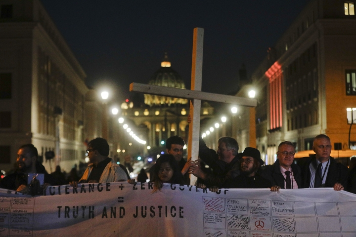 Survivors of sex abuse hold a cross as they gather in front of Via della Conciliazione, the road leading to St. Peter's Square, visible in background, during a twilight vigil prayer of the victims of sex abuse, in Rome, Thursday, Feb. 21, 2019 during a twilight vigil prayer near Castle Sant' Angelo, in Rome, Thursday, Feb. 21, 2019. Pope Francis opened a landmark sex abuse prevention summit Thursday by warning senior Catholic figures that the faithful are demanding concrete action against predator priests and not just words of condemnation. (AP Photo/Gregorio Borgia)