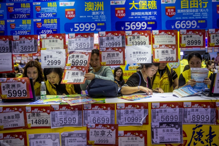 "In this March 3, 2018, photo, people check on travel packages offered by travel agencies during the Guangzhou International Travel Fair in Guangzhou in south China's Guangdong province. Travelers in China were blocked from buying plane tickets 17.5 million times last year as a penalty for failing to pay fines or other offenses. The Chinese government reported this week on penalties imposed under a controversial ""social credit"" system the ruling Communist Party says will improve public behavior. (Chinatopix via AP)"