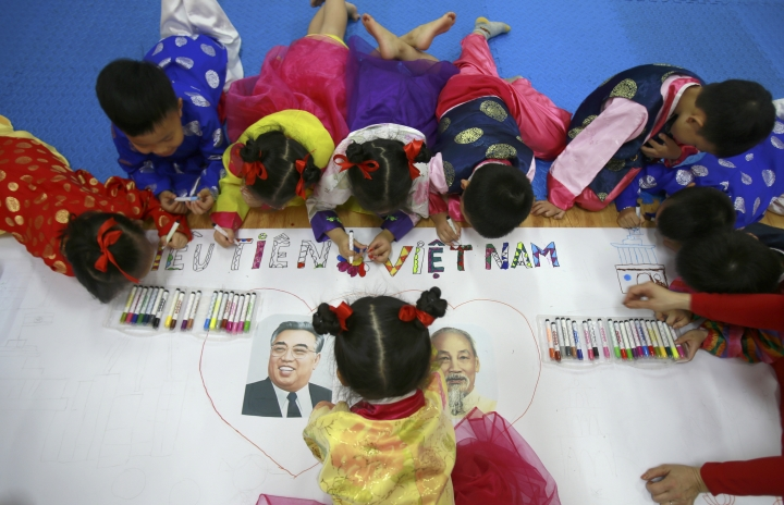 In this Thursday, Feb. 21, 2019, photo, children in Vietnamese and Korean traditional costumes color a banner with portraits of the late Vietnamese revolutionary leader Ho Chi Minh, right, and the late North Korean leader Kim Il Sung at Vietnam-Korea Friendship Kindergarten in Hanoi, Vietnam. Children at the kindergarten have been practicing singing and dancing, hoping to show off their talents to North Korean leader Kim Jong Un when he comes to town this week for his second summit meeting with U.S. President Donald Trump. (AP Photo/Hau Dinh)