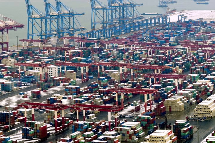 """In this Feb. 14, 2019, photo, trucks move around containers stored at a port in Qingdao in east China's Shandong province. U.S. President Donald Trump said Sunday, Feb. 24, 2019, he will extend a deadline to escalate tariffs on Chinese imports, citing """"substantial progress"""" in weekend talks between the two countries. (Chinatopix via AP)"""