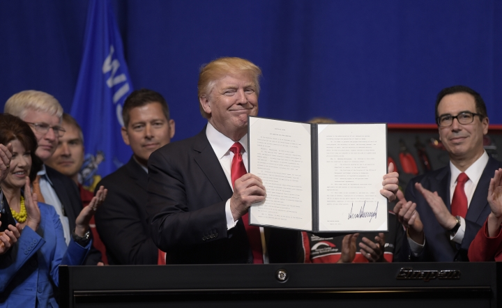 """FILE - In this April 18, 2017 file photo, President Donald Trump holds up the """"Buy American, Hire American"""" executive order which he signed during a visit to the headquarters of tool manufacturer Snap-on Inc. in Kenosha, Wis. Immigrants with specialized skills are being denied work visas or seeing applications get caught up in lengthy bureaucratic tangles under federal changes that some consider a contradiction to Trump's promise of a continued pathway to the U.S. for the best and brightest. (AP Photo/Susan Walsh)"""