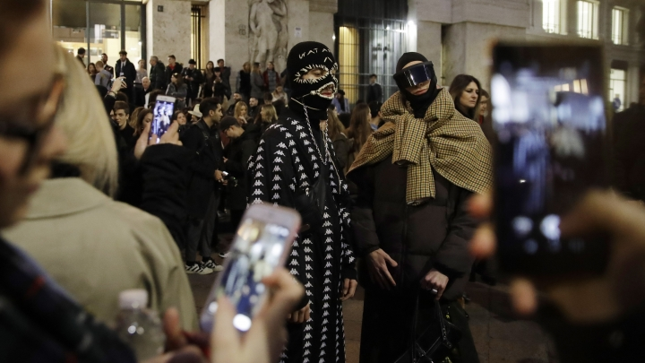 In this picture taken on Friday, Feb. 22, 2019, guests arrive to attend the Versace women's Fall-Winter 2019-2020 fashion show, that was presented in Milan, Italy. Fashion is a creative endeavor with no real boundaries, and outside each luxury runway venue, vibrant scenes unfold amid the confluence of influencers, fashion editors, celebrity guests, street photographers and hopeful selfie-snappers. (AP Photo/Luca Bruno)