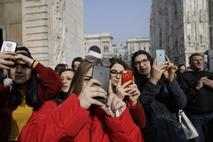 In this picture taken on Tuesday, Feb.19, 2019, teenagers shoot video and photos to guests attending the Alberto Zambelli women's Fall-Winter 2019-2020 fashion show, that was presented in Milan, Italy. Fashion is a creative endeavor with no real boundaries, and outside each luxury runway venue, vibrant scenes unfold amid the confluence of influencers, fashion editors, celebrity guests, street photographers and hopeful selfie-snappers. (AP Photo/Luca Bruno)