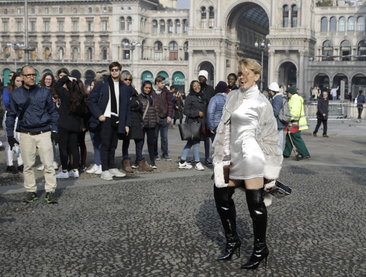 In this picture taken on Tuesday, Feb.19, 2019, Italian showgirl Justine Matera poses for photographers after the Alberto Zambelli women's Fall-Winter 2019-2020 fashion show, that was presented in Milan, Italy. Fashion is a creative endeavor with no real boundaries, and outside each luxury runway venue, vibrant scenes unfold amid the confluence of influencers, fashion editors, celebrity guests, street photographers and hopeful selfie-snappers. (AP Photo/Luca Bruno)