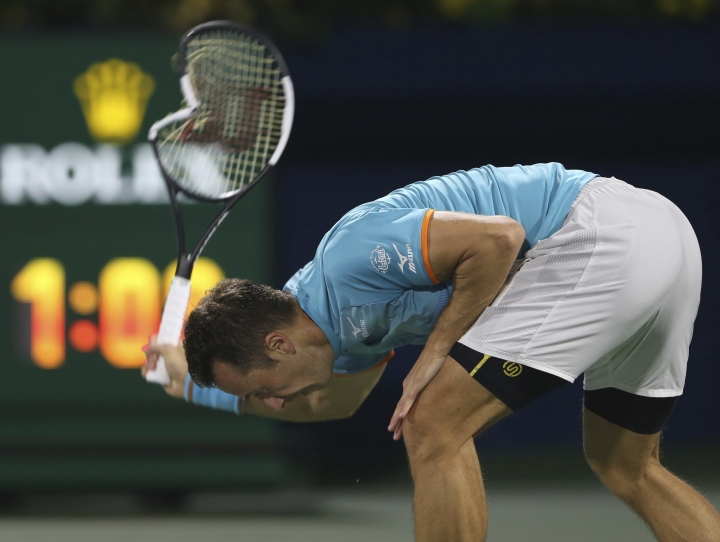 Philipp Kohlschreiber of Germany breaks his racket in a match against Roger Federer of Switzerland during the Dubai Duty Free Tennis Championship, in Dubai, United Arab Emirates, Monday, Feb. 25, 2019. (AP Photo/Kamran Jebreili)