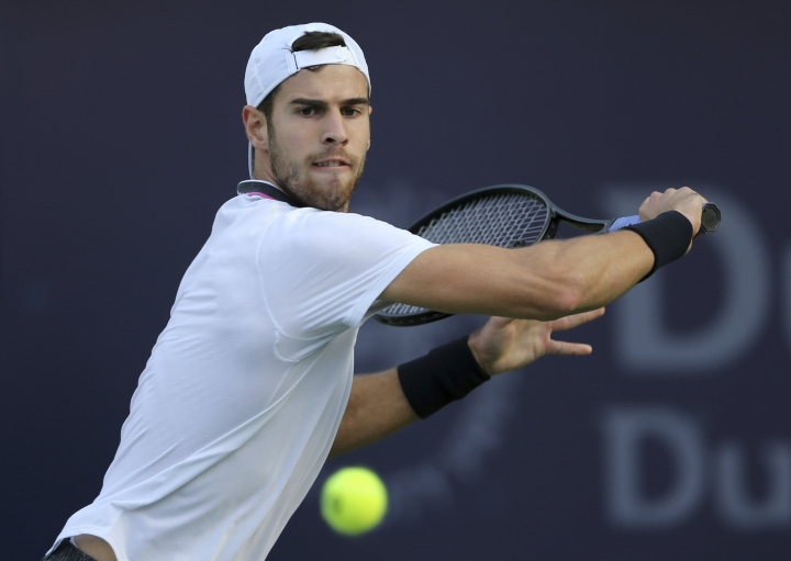 Russia's Karen Khachanov returns the ball to Georgia's Nikoloz Basilashvili during their match at the Dubai Duty Free Tennis Championship, in Dubai, United Arab Emirates, Monday, Feb. 25, 2019. (AP Photo/Kamran Jebreili)