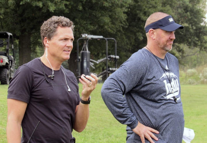 """In this 2017 file photo, director Greg Whiteley, left, and Independence Community College football coach Jason Brown watch a practice during a shoot for the Netflix series """"Last Chance U."""" in Independence, Kan. Jason Brown has resigned after an inflammatory series of text messages in which he allegedly told a German player: """"I'm your new Hitler."""" Brown said in a statement posted on social media that a story on the texts in the Montgomery County Chronicle made it """"nearly impossible to stay"""" at Independence Community College. (Dion Lefler/The Wichita Eagle via AP, File)"""