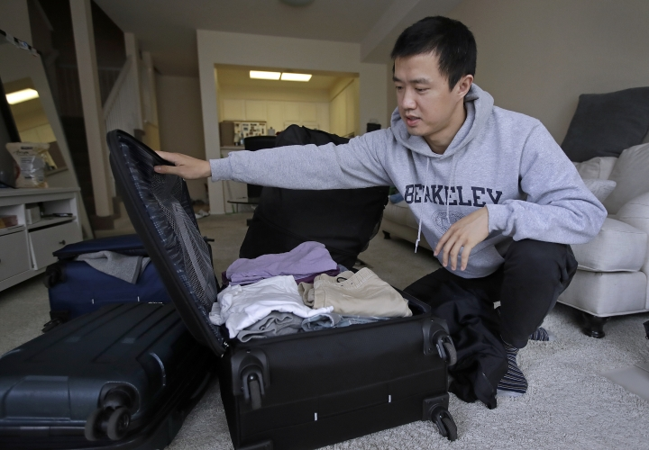 """In this Monday, Feb. 4, 2019, photo, Leo Wang packs a suitcase at his home in San Jose, Calif. Wang has found himself trapped in an obstacle course regarding H-1B work visas for foreigners. His visa denied and his days in the United States numbered, Wang is looking for work outside the country. """"I still believe in the American dream,"""" he says. """"It's just that I personally have to pursue it somewhere else."""" (AP Photo/Ben Margot)"""