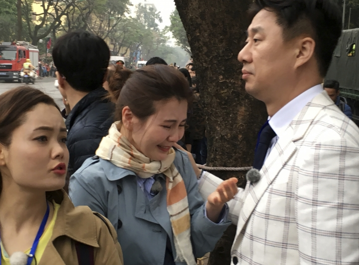 North Korean defector Shin Eun Ha, center, cries after a limousine carrying North Korean leader Kim Jong Un passes by her near a Hanoi hotel where Kim is staying, Tuesday, Feb. 26, 2019, in Hanoi, Vietnam. Nam Hee Seok, a South Korean TV talk show on North Korea, right, who is patting the back of Shin, who is a regular guest on the program. On left is another North Korean defector who appears on the program. Shin and another North Korean defector have flown to Hanoi to wish for progress during the second summit between their former leader Kim Jong Un and Trump. (AP Photo Kim Hyung-jin)