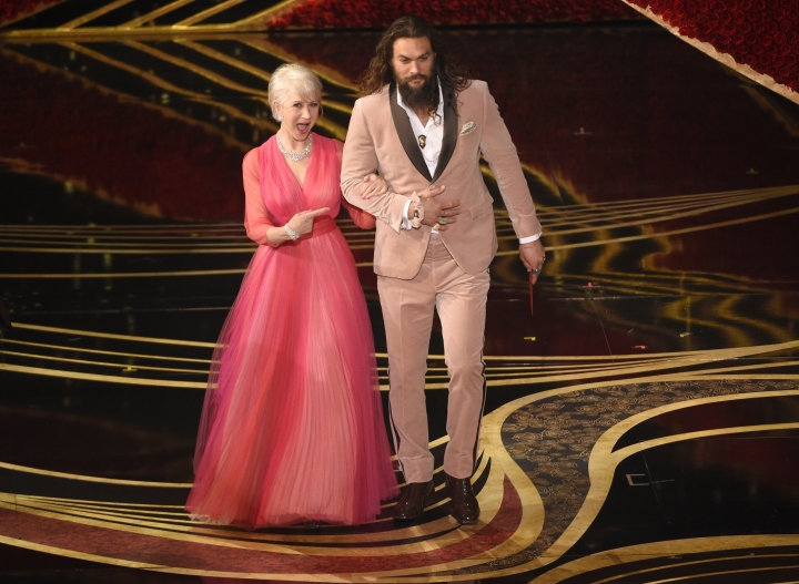 Helen Mirren, left, and Jason Momoa present the award for best documentary feature at the Oscars on Sunday, Feb. 24, 2019, at the Dolby Theatre in Los Angeles. (Photo by Chris Pizzello/Invision/AP)