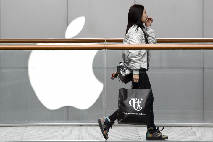 """A woman carries a paper bag containing goods purchased from American brand Abercrombie & Fitch walks past an Apple store at the capital city's popular shopping mall in Beijing, Tuesday, Feb. 26, 2019. American companies in China increasingly worry U.S.-Chinese relations will deteriorate and are """"hedging their bets"""" by delaying investment or moving operations, a business group reported Tuesday. (AP Photo/Andy Wong)"""