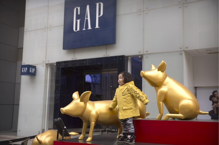 """A girl plays in a display of golden pigs for the Year of the Pig outside a store for American clothing retailer The Gap at an outdoor shopping street in Beijing, Tuesday, Feb. 26, 2019. American companies in China increasingly worry U.S.-Chinese relations will deteriorate and are """"hedging their bets"""" by delaying investments or moving operations, a business group reported Tuesday. (AP Photo/Mark Schiefelbein)"""