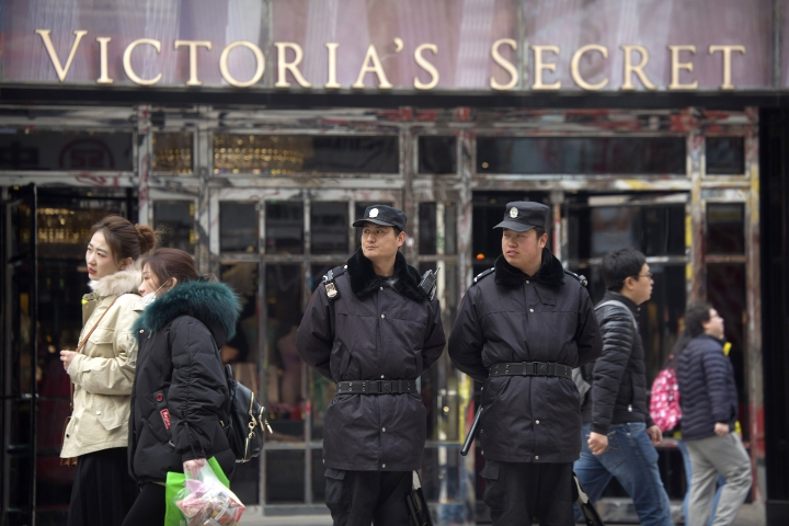 """Security officers stand guard outside a store for American lingerie retailer Victoria's Secret at an outdoor shopping street in Beijing, Tuesday, Feb. 26, 2019. American companies in China increasingly worry U.S.-Chinese relations will deteriorate and are """"hedging their bets"""" by delaying investments or moving operations, a business group reported Tuesday. (AP Photo/Mark Schiefelbein)"""