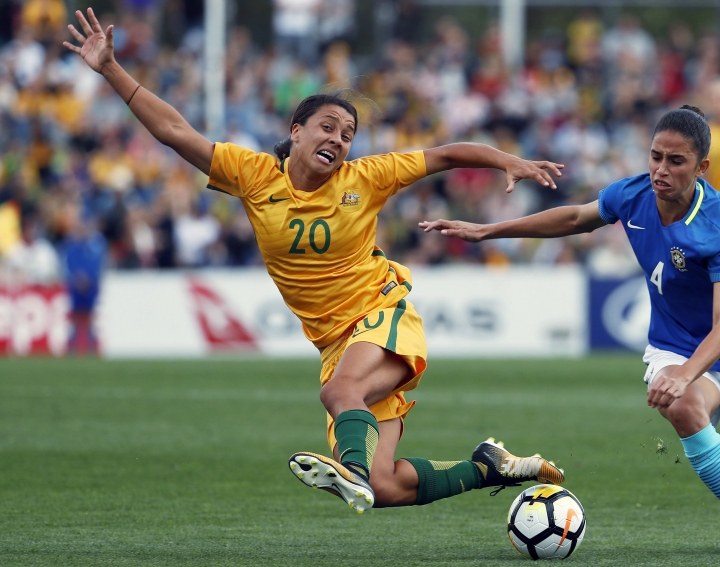 FILE - In this Sept. 16, 2017, file photo, Australia's Sam Kerr, left, fights for the ball against Brazil's Rafaelle Carvalho Souzav during their friendly soccer match in Penrith, Australia. Kerr has been named captain of the women's national soccer, Wednesday, Feb. 27, 2019, as they prepared for Thursday's first match against New Zealand in the four-team Cup of Nations tournament. (AP Photo/Daniel Munoz, File)