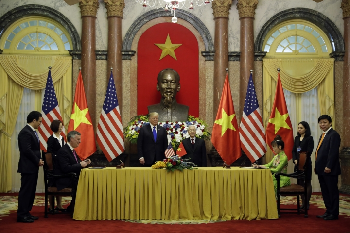 President Donald Trump and Vietnamese President Nguyen Phu Trong watch as VietJet President Nguyen Thi Phuong Thao, right, and Kevin McAllister, CEO of Boeing Commercial Airplanes, left, sign a business agreement at the Presidential Palace, Wednesday, Feb. 27, 2019, in Hanoi. (AP Photo/ Evan Vucci)