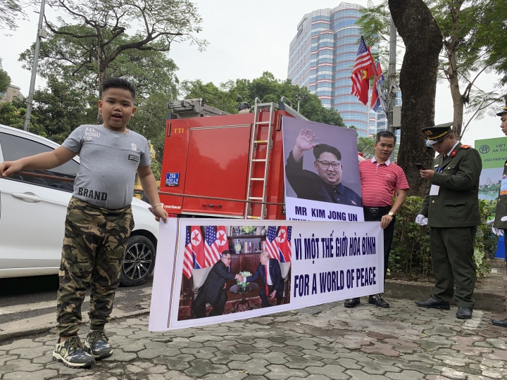 """Pham Quang Dung, 8years old, wearing a hairstyle of North Korean leader Kim Jong Un, holds a placard that reads """"For a World of Peace"""" with his father Pham Quang Trung, right, near a Hanoi hotel where Kim stays on Wednesday, Feb. 27, 2019, Hanoi, Vietnam. Kim and U.S. President Donald Trump are expected to meet for their second summit Feb. 27 and 28 in Hanoi. (AP Photo/Joeal Calupitan)"""