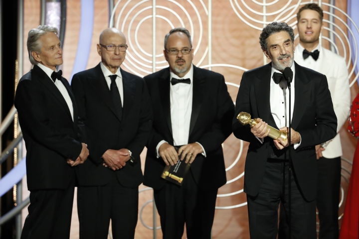 "FILE - This Jan. 6, 2019, file image originally released by NBC shows Chuck Lorre, foreground right, accepting the award for best TV comedy series for Netflix's ""The Kominsky Method"" during the 76th Annual Golden Globe Awards in Beverly Hills, Calif. Lorre is one of the most successful comedy producers in TV history, with an estimated net worth of more than $600 million for making shows including ""The Big Bang Theory,"" ""Two and a Half Men"" and ""Mom"" for CBS. Yet he'd never won an Emmy or Golden Globe. (Paul Drinkwater/NBC via AP, File)"