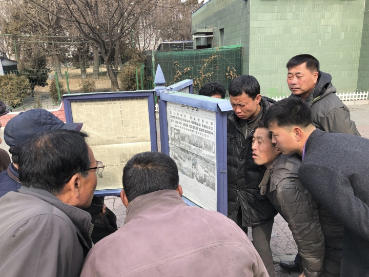 In this Wednesday, Feb. 27, 2019, photo, men gather around the public newspaper posts to read about North Korean leader Kim Jong Un's visit to Vietnam for the second summit with U.S. President Donald Trump, in Pyongyang, North Korea. North Koreans have been getting a quicker, more polished look at their leader as he meets with Trump in Hanoi in their second summit. But one thing hasn't changed at all - North Korea's media have one story to tell, and it's always about the infallibility of the glorious leader. (AP Photo)