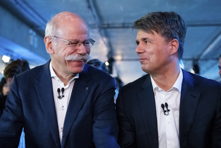 File -- In this Friday, Feb. 22, 2019 photo Harald Krueger, right, CEO of the car manufacturer BMW, and Dieter Zetsche, left, CEO of the Daimler stock company and the car manufacturer Mercedes Benz, talk during a press conference in Berlin, Germany. Automakers BMW and Daimler said on Thursday, Feb 28, 2019 they will work together on developing the automated driving technology expected to transform the industry in the years ahead. (Bernd von Jutrczenka/dpa via AP, file)