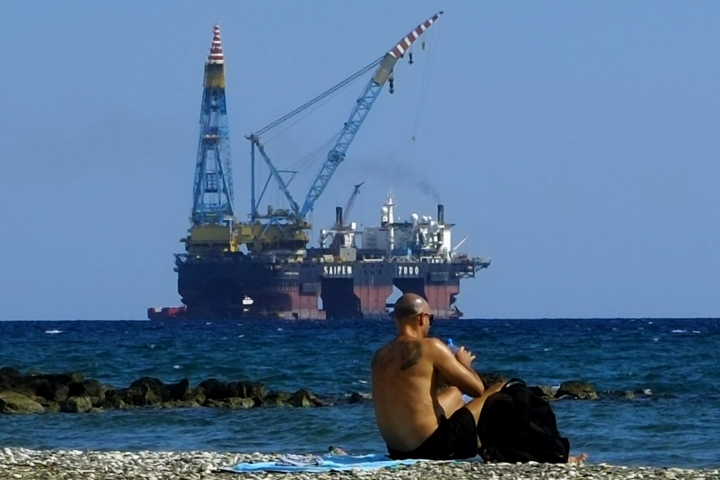 """FILE - In this Sunday, Oct. 15, 2017 file photo, a man sits on a beach as a drilling platform is seen in the background outside from Larnaca port, in the eastern Mediterranean island of Cyprus. Cyprus' energy minister says ExxonMobil has discovered the third-biggest gas deposit in the world in the last two years. Announcing the results on Thursday, Feb. 28, 2019, of exploratory drilling, Energy Minister Georgios Lakkotrypis said the """"world class"""" discovery offers proof of the potential for more hydrocarbon discoveries in waters off the east Mediterranean island nation that could become an alternative energy source for Europe. (AP Photo/Petros Karadjias, File)"""