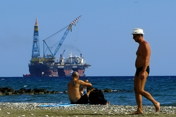 "FILE - In this Sunday, Oct. 15, 2017 file photo, people on a beach as a drilling platform is seen in the background outside from Larnaca port, in the eastern Mediterranean island of Cyprus. Cyprus' energy minister says ExxonMobil has discovered the third-biggest gas deposit in the world in the last two years. Announcing the results on Thursday, Feb. 28, 2019, of exploratory drilling, Energy Minister Georgios Lakkotrypis said the ""world class"" discovery offers proof of the potential for more hydrocarbon discoveries in waters off the east Mediterranean island nation that could become an alternative energy source for Europe. (AP Photo/Petros Karadjias, File)"