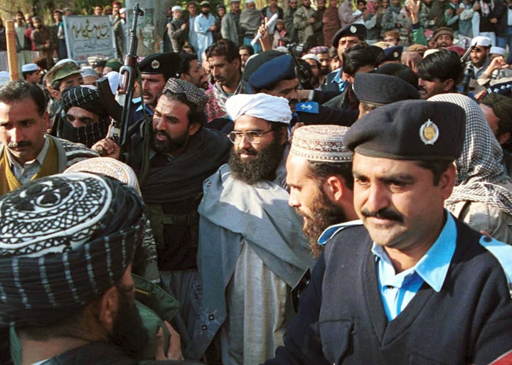 FILE - In this Jan. 27, 2000 file photo, Masood Azhar, center, (wearing glasses and white turban), leader of Jaish-e-Mohammad arrives in Islamabad, Pakistan. When a suicide bomber blew himself up on Feb. 14, 2019, killing more than 40 soldiers in India's insurgency wracked Kashmir region, the militant group Jaish-e-Mohammad was quick to take responsibility. The Pakistan-based group's attack in Kashmir sent tensions soaring between the two nuclear armed neighbors. (AP Photo/Mian Khursheed, File)