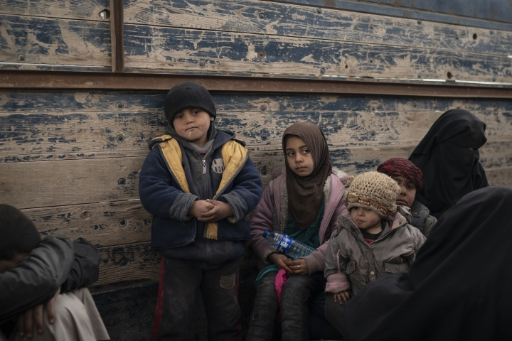 Women and children wait to be screened by U.S.-backed Syrian Democratic Forces (SDF) after being evacuated out of the last territory held by Islamic State militants, in the desert outside Baghouz, Syria, Wednesday, Feb. 27, 2019. (AP Photo/Felipe Dana)
