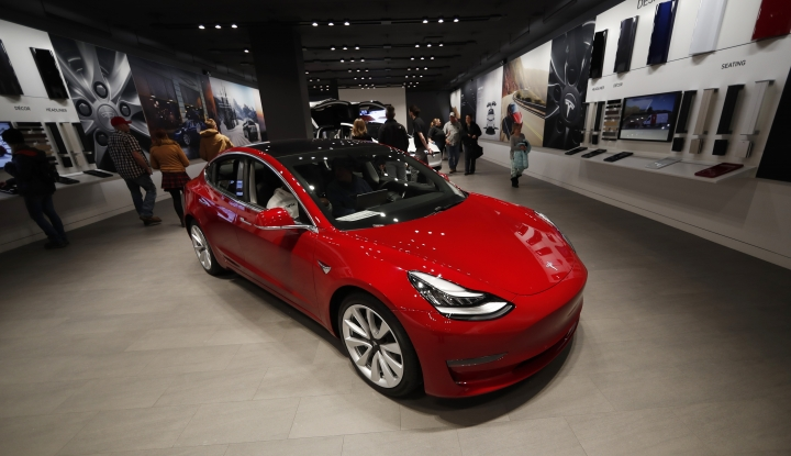 FILE - In this Feb. 9, 2019, file photograph, buyers look over a Model 3 in a Tesla store in Cherry Creek Mall in Denver. Tesla is shifting all of its sales from stores to the internet, saying the move is needed to cut costs so it can sell the mass-market Model 3 for a starting price of $35,000. The Palo Alto, California, company announced the change Thursday, Feb. 28. (AP Photo/David Zalubowski, File)