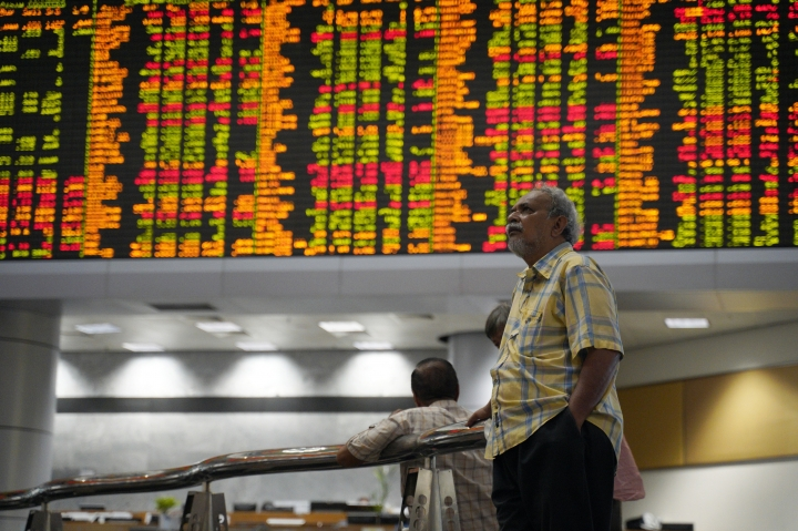 Visitors stand in front of private stock trading boards at a private stock market gallery in Kuala Lumpur, Malaysia, Friday, March 1, 2019. Asian stocks were mostly higher on Friday after a report suggested that the leaders of China and the U.S. could be endorsing a trade deal in weeks. (AP Photo/Yam G-Jun)