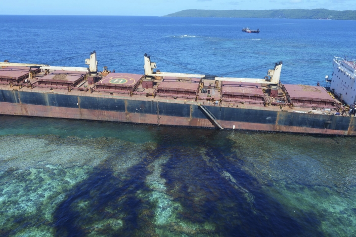 "In this Feb. 26, 2019, photo taken by the Australian Maritime Safety Authority near Rennell Island in the Solomon Islands shows the ""MV Solomon Trader"" ship which ran aground Feb. 5. Australian officials say an environmental disaster is unfolding in the Solomon Islands after the ship ran aground and began leaking oil next to a UNESCO World Heritage site. (The Australian High Commission Solomon Islands via AP)"