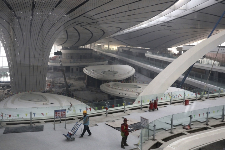 Workers past through the terminal of the Beijing Daxing International Airport under construction on the outskirts of Beijing, China, Friday, March 1, 2019. Construction on the new airport in China's capital which promises to be one of the world's largest is speeding toward completion.(AP Photo/Ng Han Guan)