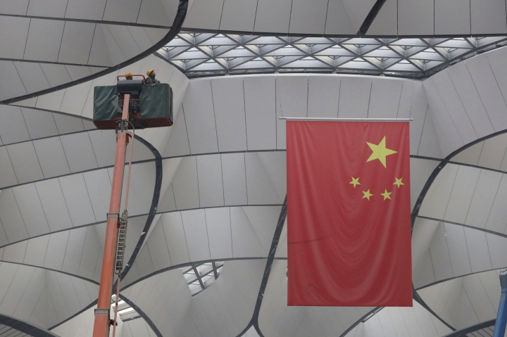 Workers check the roof during construction of the Beijing Daxing International Airport on the outskirts of Beijing, China, Friday, March 1, 2019. Construction on the new airport in China's capital which promises to be one of the world's largest is speeding toward completion. (AP Photo/Ng Han Guan)