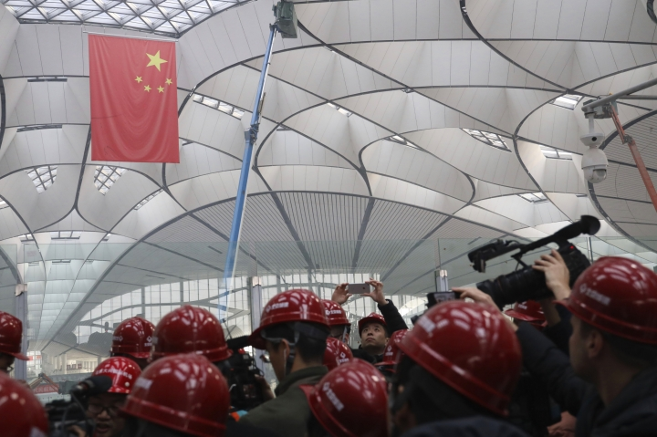 Visitors tour the Beijing Daxing International Airport under construction on the outskirts of Beijing, China, Friday, March 1, 2019. Construction on the new airport in China's capital which promises to be one of the world's largest is speeding toward completion. (AP Photo/Ng Han Guan)