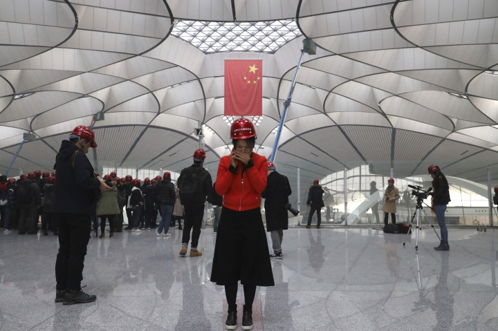 A woman talks on her phone in the terminal of the Beijing Daxing International Airport under construction on the outskirts of Beijing, China, Friday, March 1, 2019. Construction on the new airport in China's capital which promises to be one of the world's largest is speeding toward completion. (AP Photo/Ng Han Guan)
