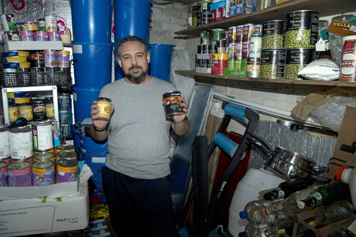 """Melvin Burton holds up stored provisions in his garden shed in Littleport, Cambridgeshire, England, Friday March 1, 2019. For almost as long as Britain and the European Union have been wrangling over Brexit, Burton has been preparing for a bumpy landing. He's growing vegetables, drying fruit and buying in bulk. He reels off the cornucopia of cans filling his shed and the cupboard under his stairs: """"Tomato sauce, chopped tomatoes, corned beef, tuna, honey, baked beans, tins of ham. (AP Photo/Jo Kearney)"""