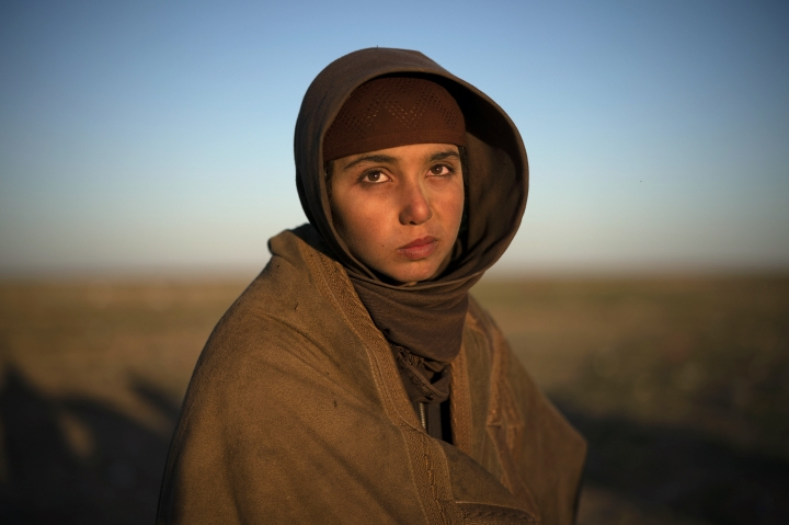 A girl waits to be screened by U.S.-backed Syrian Democratic Forces (SDF) after being evacuated out of the last territory held by Islamic State militants, in the desert outside Baghouz, Syria, Friday, March 1, 2019. (AP Photo/Felipe Dana)
