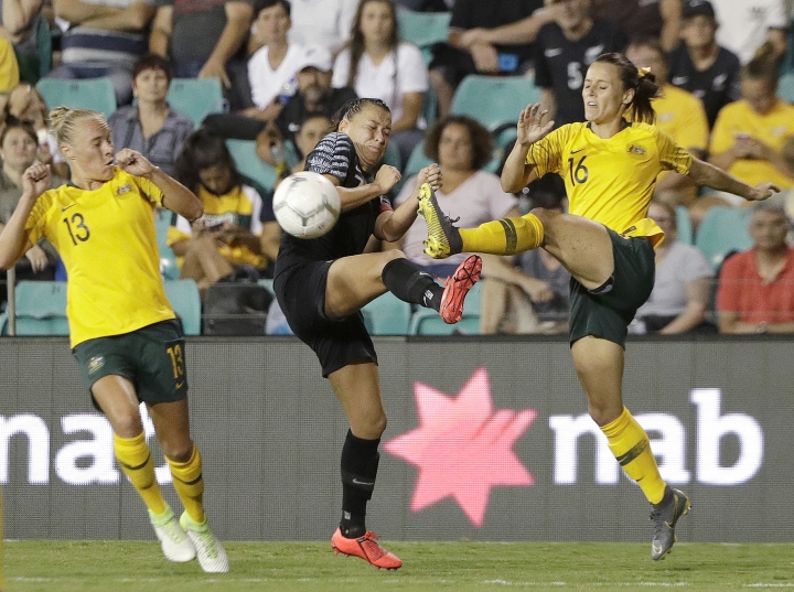 Australia's Hayley Raso, right, clears the ball past New Zealand's Ali Riley, center, during their Cup of Nations soccer game in Sydney, Thursday, Feb. 28, 2019. (AP Photo/Rick Rycroft)
