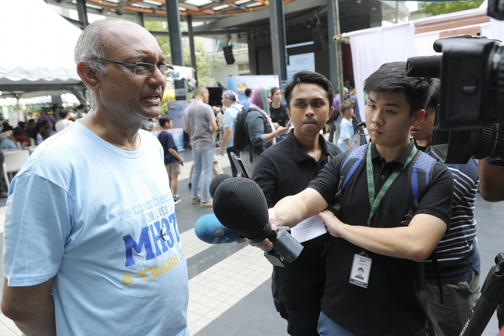 KS Narendran, left, husband of Chandrika Sharma who was a passenger of the missing Malaysia Airlines Flight 370, is interviewed during a Day of Remembrance for MH370 event in Kuala Lumpur, Malaysia, Sunday, March 3, 2019. Transport Minister Anthony Loke said the government is open to proposals to resume the search for MH370 as families of passengers marked the fifth anniversary of the jet's disappearance. (AP Photo/Vincent Thian)