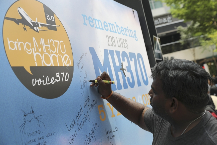 A man writes a condolence message during a Day of Remembrance for MH370 event in Kuala Lumpur, Malaysia, Sunday, March 3, 2019. Five years ago, Malaysia Airlines Flight MH370, a Boeing 777, had gone missing the day before while over the South China Sea with 239 people on board. (AP Photo/Vincent Thian)