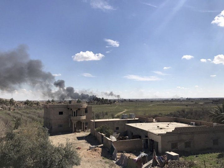 Columns of black smoke rise from the last small piece of territory held by Islamic State militants as U.S. backed fighters pound the area with artillery fire and occasional airstrikes, as seen from outside Baghouz, Syria, Sunday, March 3, 2019. Commanders of a U.S.-backed Syrian force fighting the Islamic State group in Syria say intense fighting is taking place as fighters advance toward the last piece of territory held by the extremists. (AP Photo/Sarah El-Deeb)