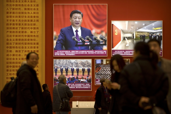 In this March 1, 2019, photo, people look at a display with photos of Chinese President Xi Jinping at an exhibition commemorating the 40th anniversary of China's Reform and Opening Up Movement at the National Museum in Beijing. In an unusual step, China's ceremonial legislature is due to endorse a law meant to help end a bruising tariff war with Washington by discouraging officials from pressuring foreign companies to hand over technology.(AP Photo/Mark Schiefelbein)