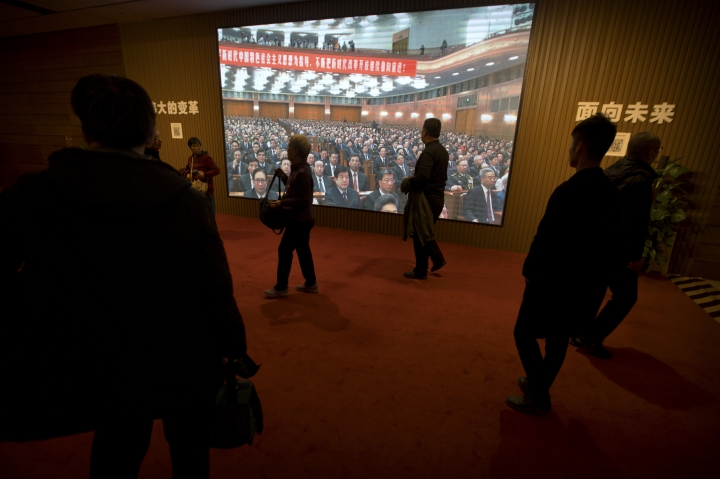 In this March 1, 2019, photo, people walk past a video display showing a meeting at the Great Hall of the People at an exhibition commemorating the 40th anniversary of China's Reform and Opening Up Movement at the National Museum in Beijing. China's ceremonial legislature is due to endorse a law Beijing hopes might help to defuse a bruising tariff war with Washington by discouraging officials from pressuring foreign companies to hand over technology. The fight with China's biggest trading partner is overshadowing the National People's Congress. (AP Photo/Mark Schiefelbein)