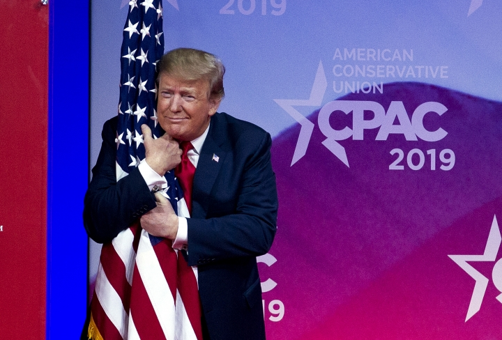 President Donald Trump hugs the American flag as he arrives to speak at Conservative Political Action Conference, CPAC 2019, in Oxon Hill, Md., Saturday, March 2, 2019. (AP Photo/Jose Luis Magana)