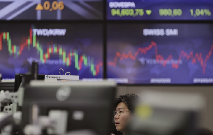 A currency trader watches computer monitors at the foreign exchange dealing room in Seoul, South Korea, Monday, March 4, 2019. Asian stocks rose Monday after news reports said Washington and Beijing are close to reaching an agreement as early as this month to end their costly tariff war. (AP Photo/Lee Jin-man)