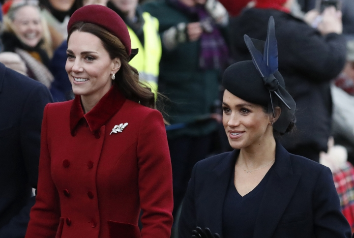 FILE - In this Tuesday, Dec. 25, 2018 file photo, Britain's Kate, Duchess of Cambridge, left, and Meghan, Duchess of Sussex arrive to attend the Christmas day service at St Mary Magdalene Church in Sandringham in Norfolk, England. Britain's royal family is warning that it will block trolls posting offensive messages on its social media channels _ and may report offenders to the police. Buckingham Palace, Clarence House and Kensington Palace issued new guidelines on Monday, March 4, 2019 spelling out the policy banning offensive, hateful and racist language.(AP Photo/Frank Augstein, File)