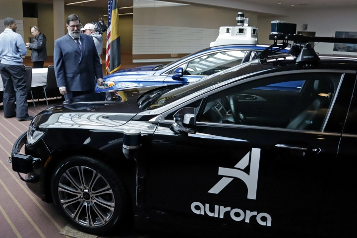 Pittsburgh Mayor William Peduto, left, checks out autonomous vehicles designed by Aurora Innovations, front, and Argo AI, rear, after signing an executive order outlining objectives and expectations for the safe testing and development of autonomous vehicles in Pittsburgh, Monday, March 4, 2019. (AP Photo/Gene J. Puskar)