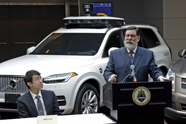 Pittsburgh Mayor William Peduto, right, stands in front of an autonomous vehicle designed by Uber as he makes remarks before signing an executive order outlining objectives and expectations for the safe testing and development of autonomous vehicles in Pittsburgh, Monday, March 4, 2019. Five companies presently developing autonomous vehicles in Pittsburgh were present for the signing. (AP Photo/Gene J. Puskar)