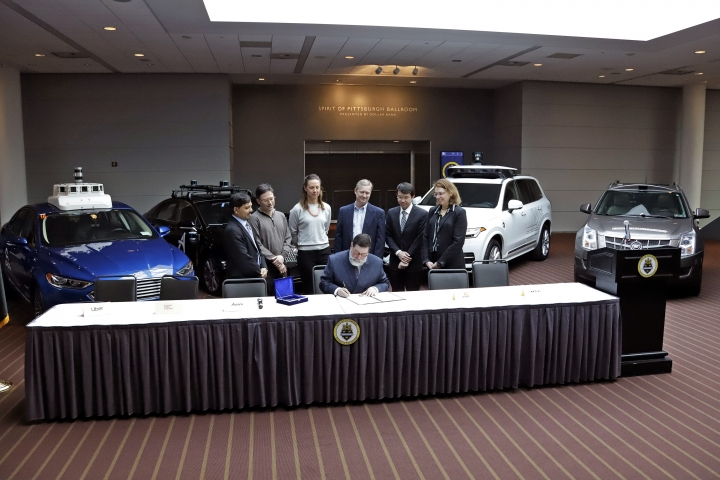 Representatives of five companies currently developing autonomous automobiles in Pittsburgh, watch as Pittsburgh Mayor William Peduto, seated center, signs an executive order outlining objectives and expectations for the safe testing and development of autonomous vehicles in Pittsburgh, Monday, March 4, 2019. The five companies are Aptiv, Argo AI, Aurora Innovation, Carnegie-Mellon and Uber. (AP Photo/Gene J. Puskar)