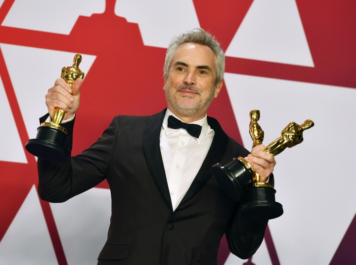 """FILE - In this Sunday, Feb. 24, 2019, file photo, Alfonso Cuaron poses with the awards for best director for """"Roma,"""" best foreign language film for """"Roma,"""" and best cinematography for """"Roma"""" in the press room at the Oscars at the Dolby Theatre in Los Angeles. """"Roma"""" may not have won the best picture Oscar this year, but it came close enough to make some of Hollywood's top players worry about Netflix's infiltration of their most prestigious award. (Photo by Jordan Strauss/Invision/AP, File)"""
